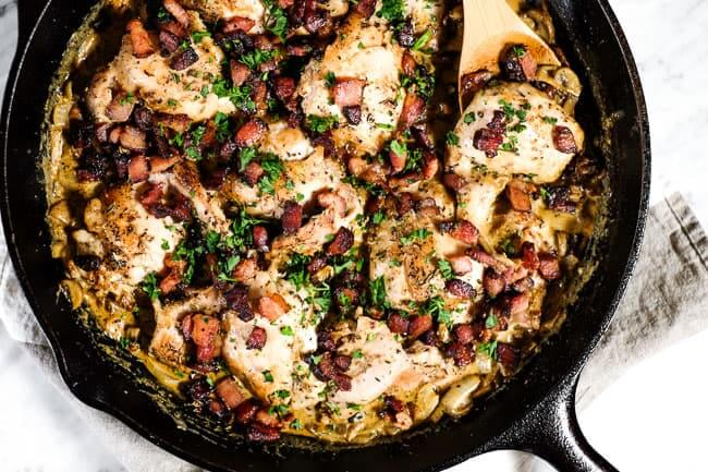 Creamy garlic chicken skillet with bacon and parsley in cast iron skillet with a serving spoon.