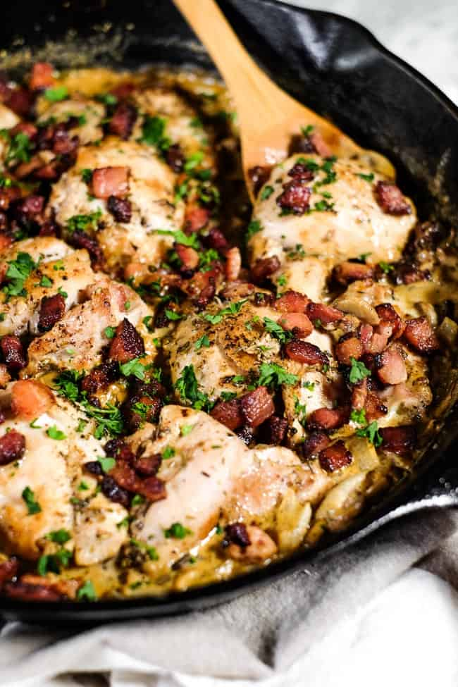 Angled shot of creamy garlic chicken with bacon and parsley in cast iron skillet with serving spoon.