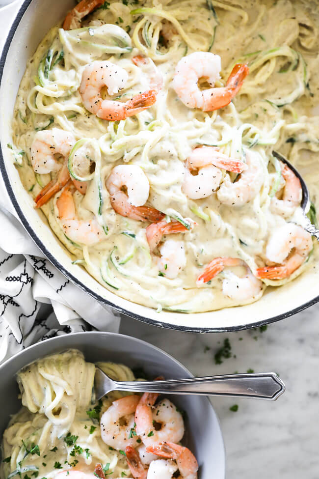 Close up image vertical overhead image of creamy garlic shrimp in skillet with some also served in a bowl.
