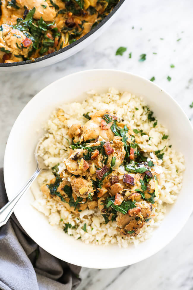 Overhead vertical image of creamy mustard chicken served in a bowl over cauliflower rice with a fork in the bowl.