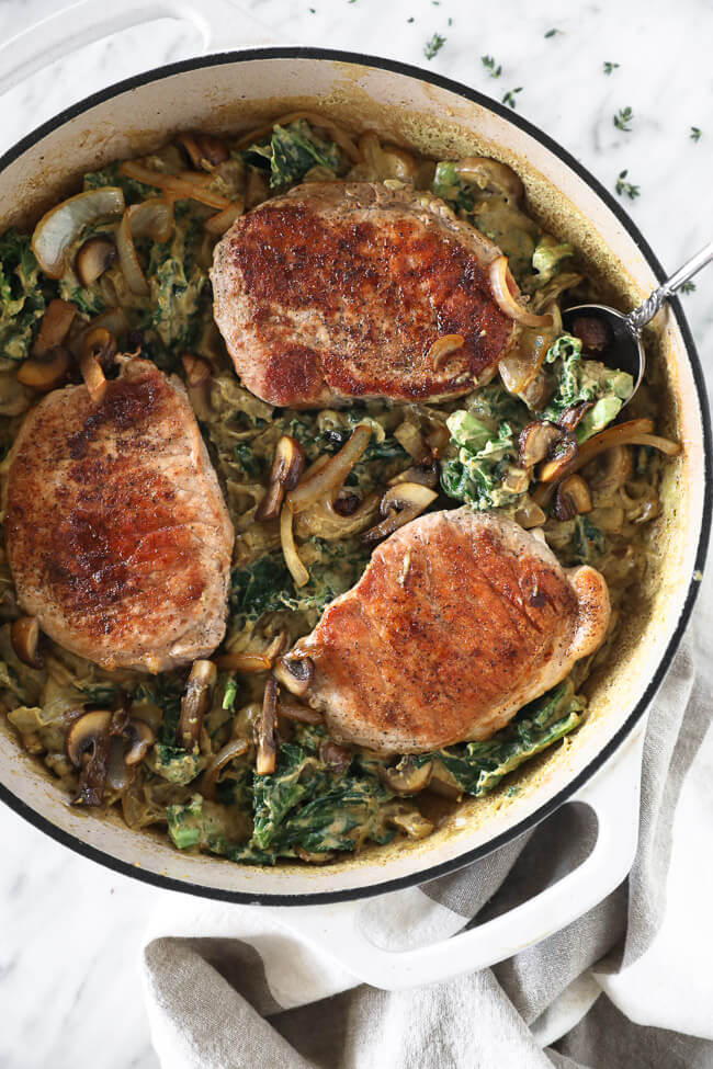 Vertical overhead image of pork chops in a creamy sauce in a skillet with a serving spoon.
