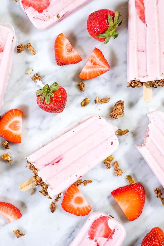 Creamy strawberry popsicles with granola on the bottom and fresh strawberries