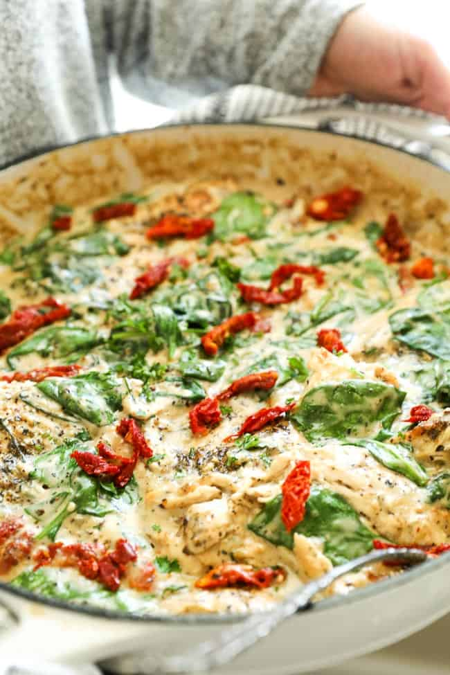 Creamy tuscan chicken in skillet someone holding skillet