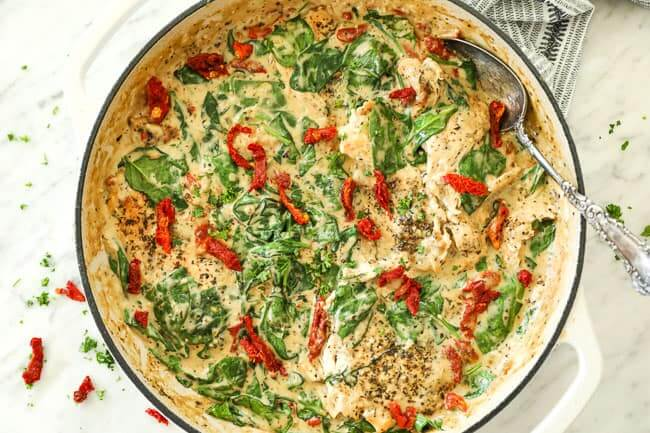 Horizontal image of creamy tuscan chicken in skillet with serving spoon in dish. Topped with more sun-dried tomatoes and fresh parsley.