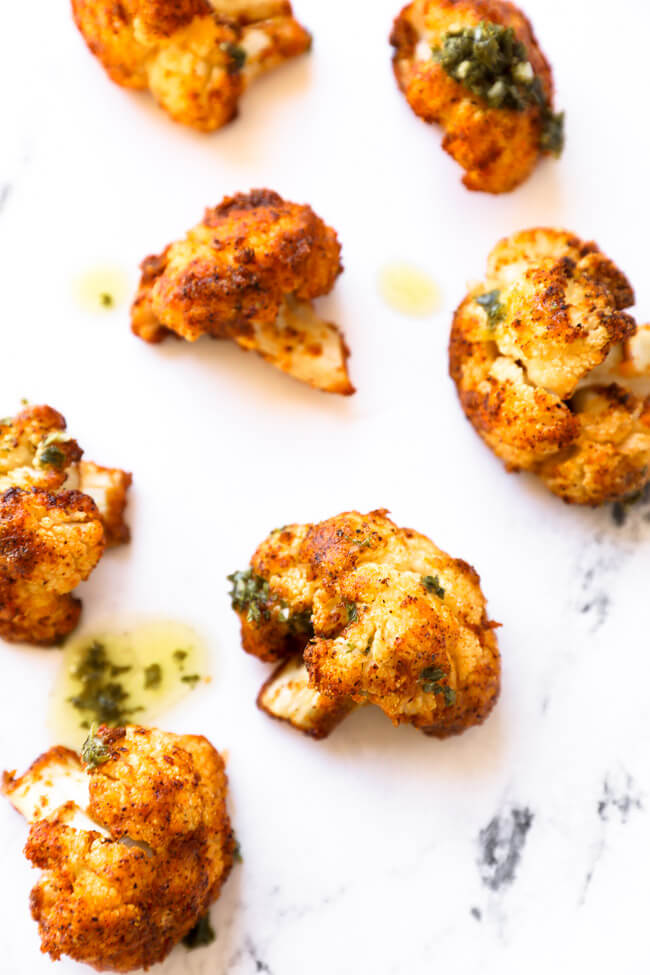 Close up of four roasted cauliflower florets on white marble