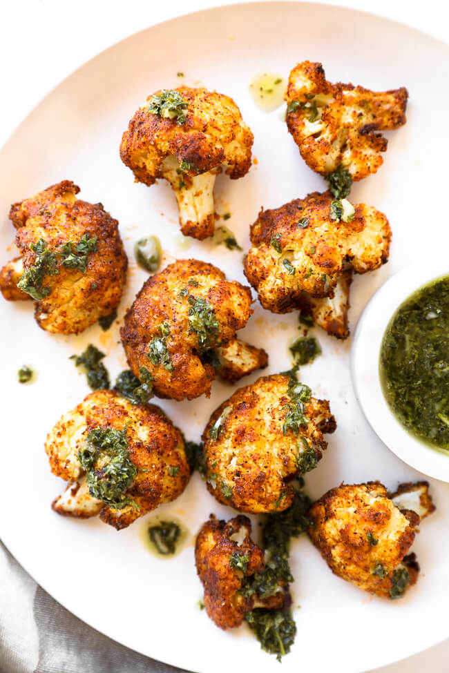 Crispy air fryer cauliflower on a white plate with green sauce on top and on the side