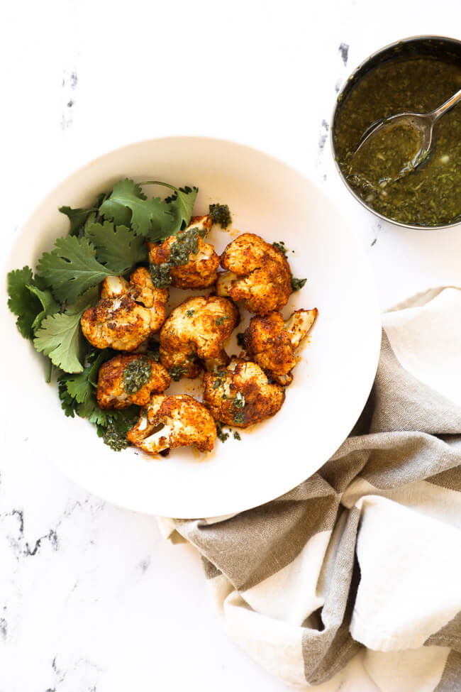 Bowl of air fryer cauliflower with parsley garnish and green sauce on the side