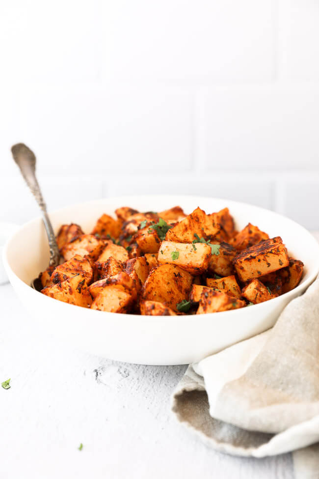 Crispy oven roasted spanish potatoes in a bowl with spoon sticking out straight on angle