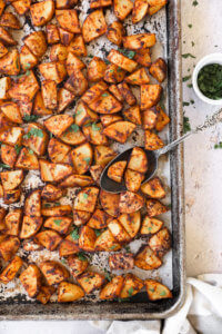 Crispy oven roasted spanish potatoes on a sheet pan with a spoon in potatoes