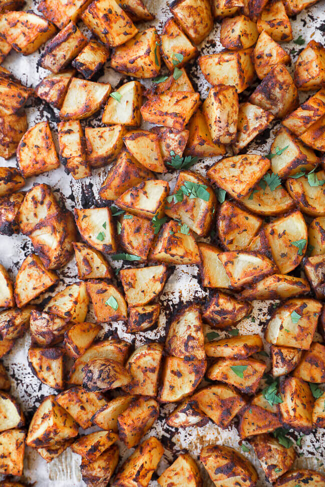 Crispy oven roasted spanish potatoes on a sheet pan close up vertical image