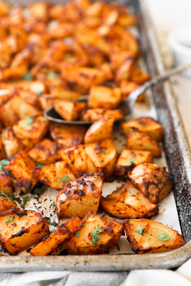 Crispy oven roasted spanish potatoes on a sheet pan with a spoon in potatoes close up angle image
