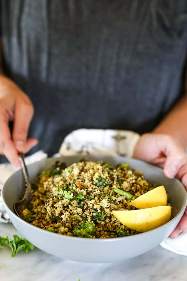 Holding a bowl of crispy roasted cauliflower rice with lemon wedges in it and scooping some out.