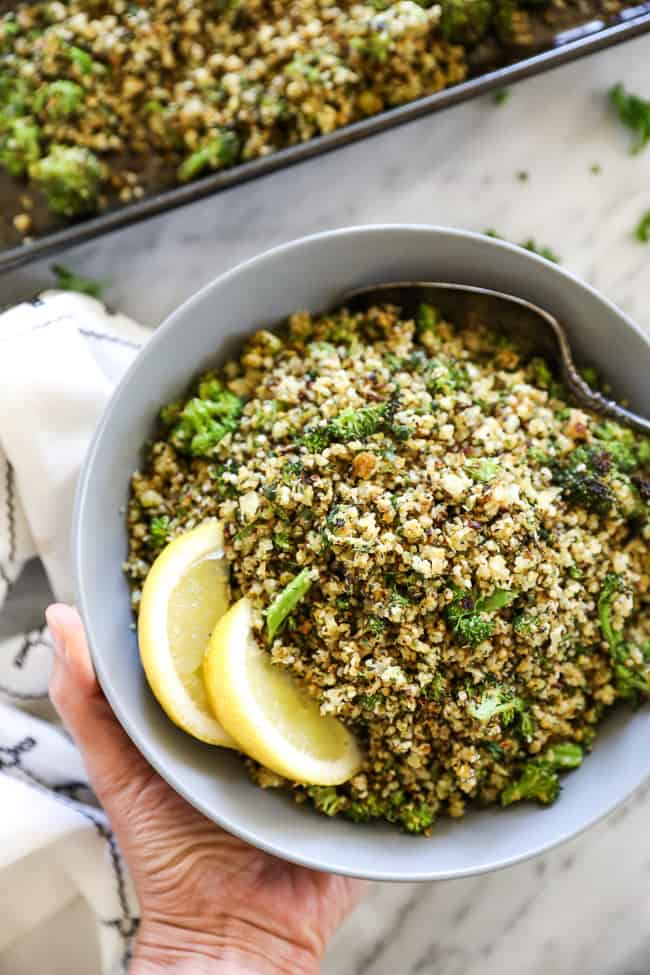 Holding a bowl of crispy roasted cauliflower rice with a serving spoon and lemon wedges in it.