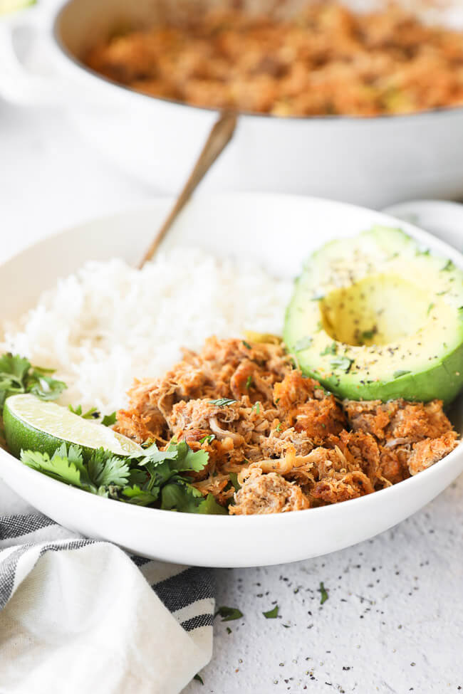 Close up angled image of crockpot mexican chicken in a bowl served with rice and avocado. Garnished with a lime wedge and fresh cilantro.