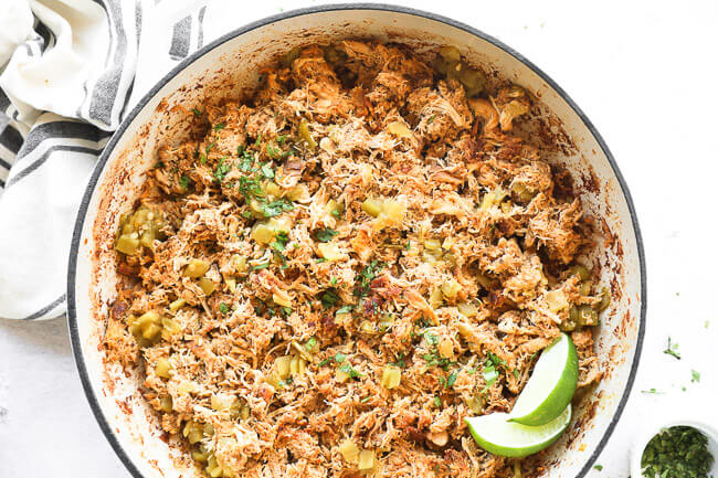 Horizontal image of crockpot mexican chicken in a skillet after being re-heated. Garnished with chopped cilantro and lime wedges.