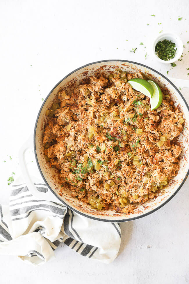 Vertical overhead image of crockpot mexican chicken in a skillet after re-heating. Garnished with cilantro and lime wedges.