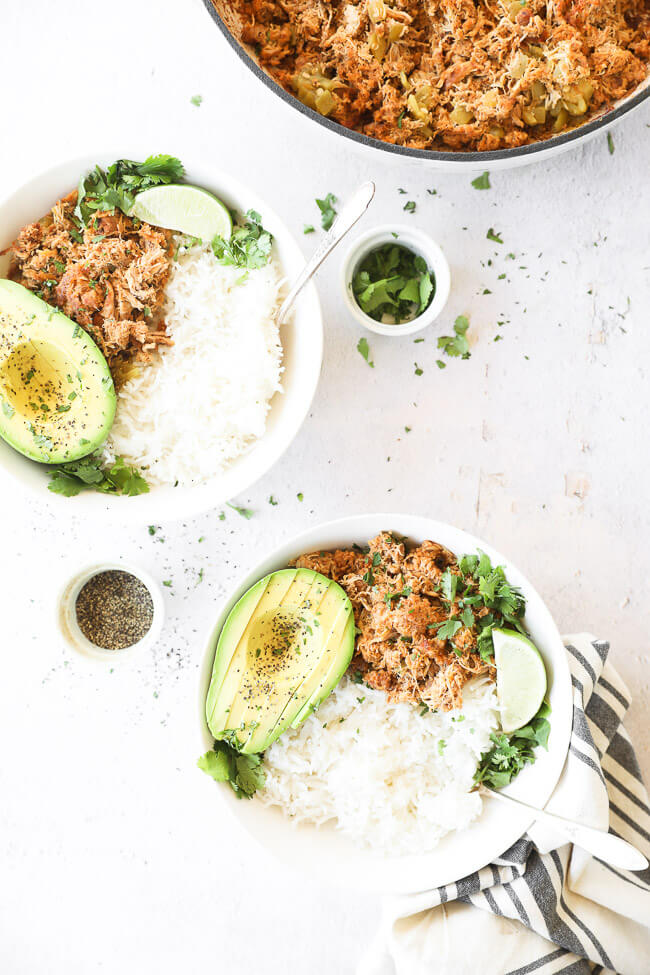 Vertical overhead image of mexican chicken served in two bowls with rice and avocado. Garnished with fresh cilantro and a lime wedge.
