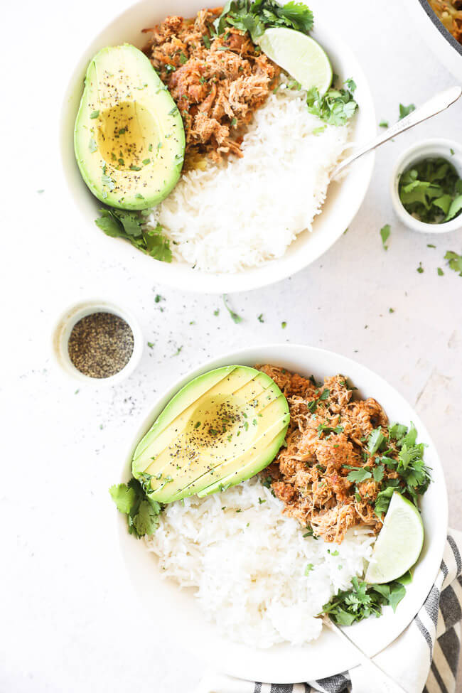 Vertical overhead image of two bowls with mexican chicken, rice and avocado. Garnished with a lime wedge and and fresh cilantro.
