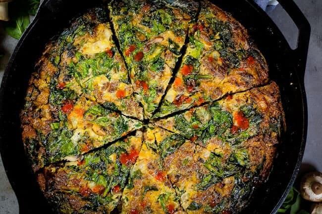 Crustless spinach quiche overhead in pan sliced horizontal with hot sauce