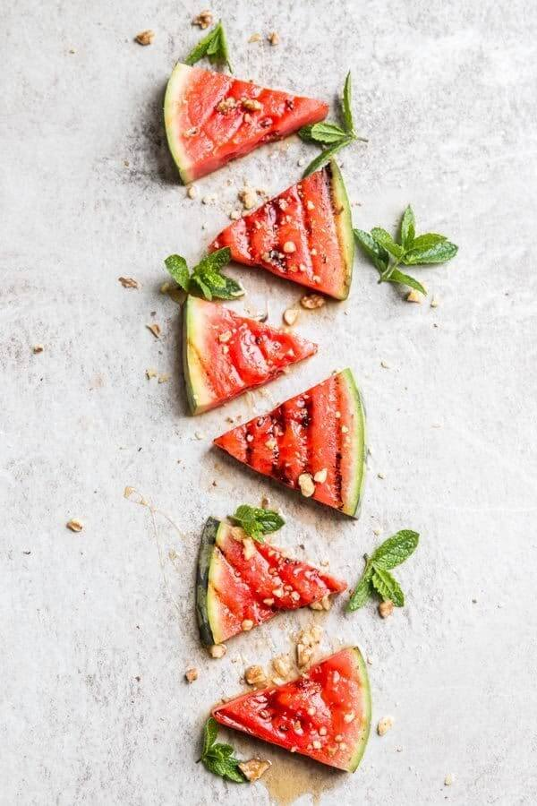 Grilled watermelon wedges in a vertical line with mint and chopped nuts
