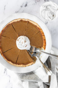 Dairy free and gluten free pumpkin pie in pie dish with whipped coconut cream on top. One slice of pie missing from dish and two forks dug into the missing spot.
