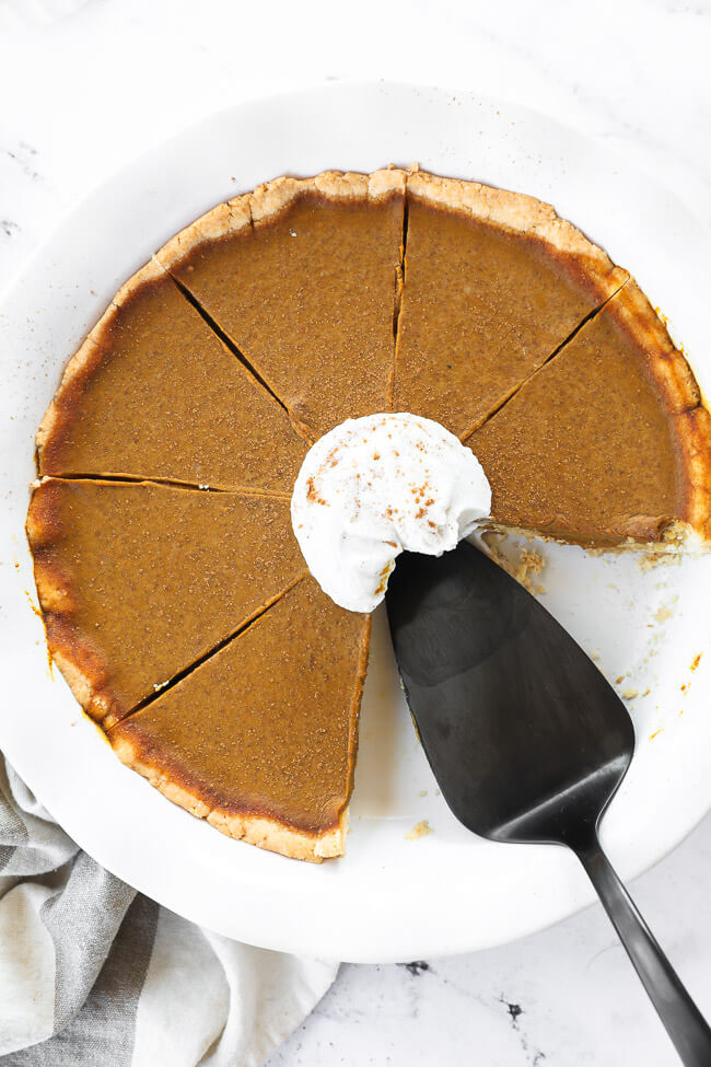 Overhead image of dairy free and gluten free pumpkin pie in pie dish with two slices removed and pie server in dish. A dollop of whipped coconut cream and cinnamon on top.
