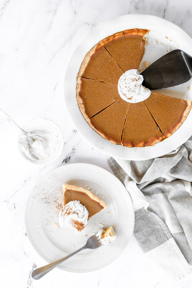 Dairy free and gluten free pumpkin pie in dish with a piece served up on a plate. Topped with whipped cream and cinnamon and a bite taken out of the slice.