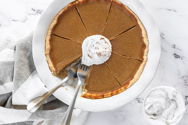 Horizontal image of dairy free and gluten free pumpkin pie in pie dish with whipped coconut cream on top. One slice of pie missing from dish and two forks dug into the missing spot.
