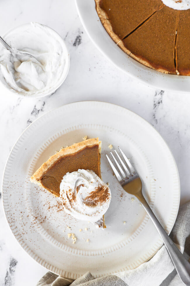 Closer up image of one piece of dairy free and gluten free pumpkin pie on a plate with a fork. Topped with whipped coconut cream and cinnamon.