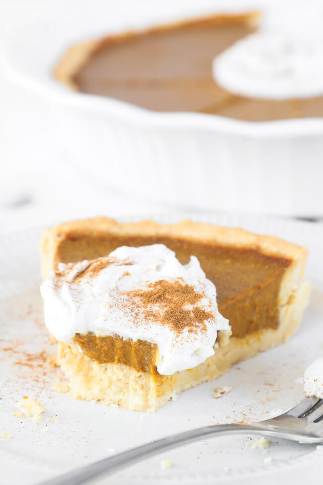 Angled image of one slice of dairy free and gluten free pumpkin pie with whipped coconut cream and cinnamon on top. A bite taken out of the slice.