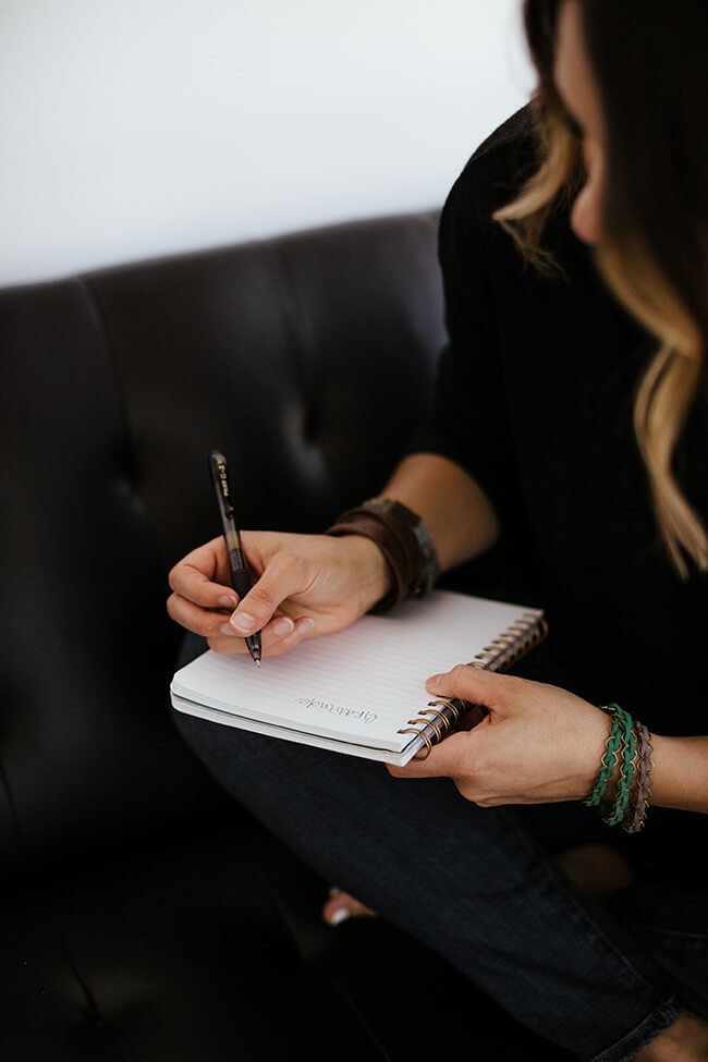 Female sitting on a couch journaling