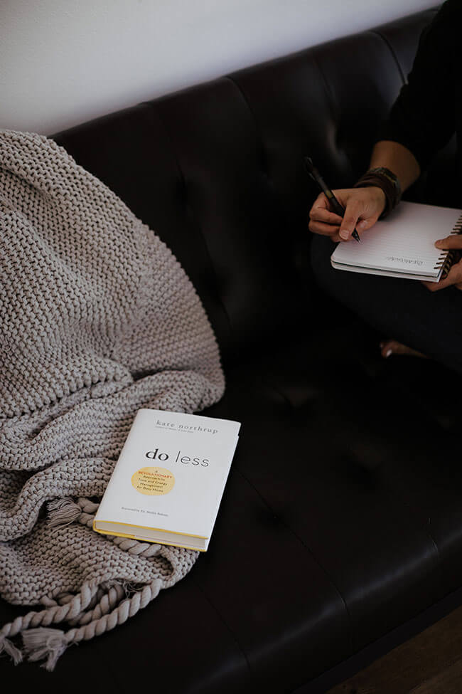 Book on couch with person at side writing in a journal