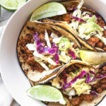 Three ground pork tacos with cabbage and avocado slaw in a bowl with lime wedges.