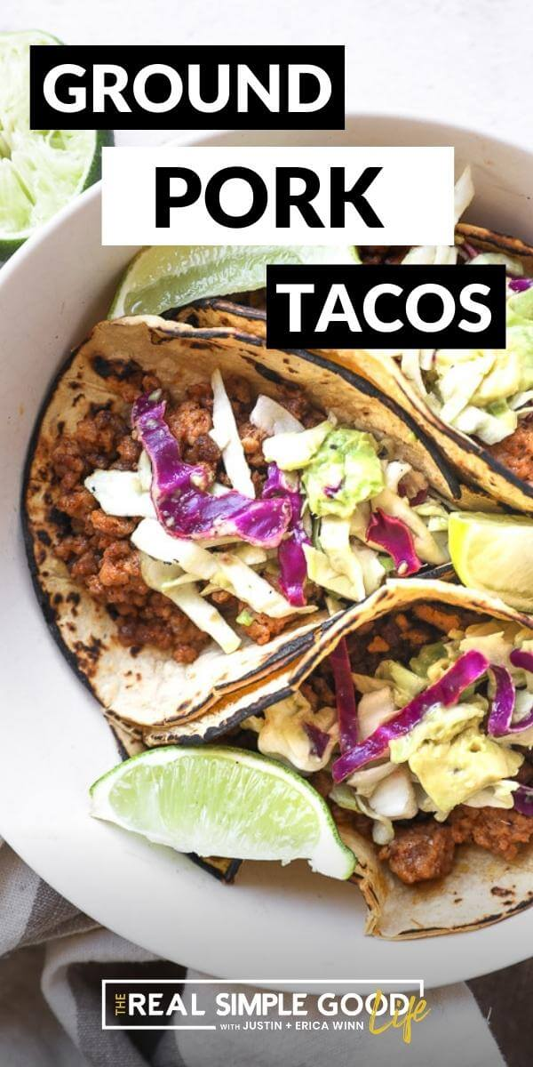 Vertical image with text overlay at the top. A bowl with three ground pork tacos with cabbage and avocado slaw  and lime wedges.