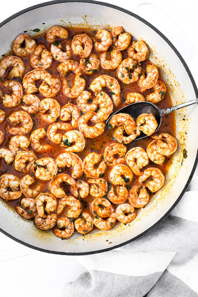 Overhead image of chili lime shrimp in skillet with a serving spoon and cilantro on top.