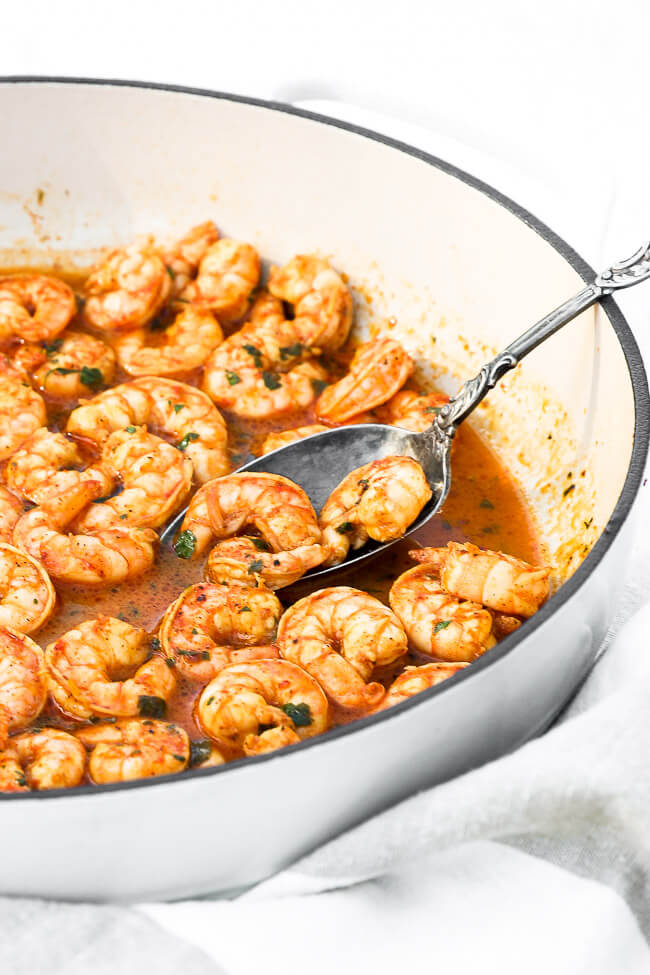 Angled image of chili lime shrimp in a skillet with a few pieces scooped up in a serving spoon in the dish.