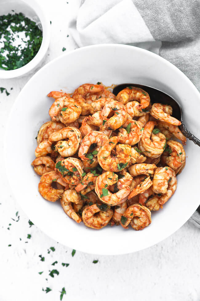 Overhead image of chili lime shrimp piled up in a bowl with a serving spoon. Topped with chopped cilantro.