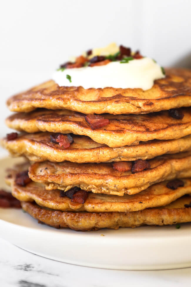 stack of bacon pancakes on a plate with sour cream, chives, more bacon and shredded cheese on top.