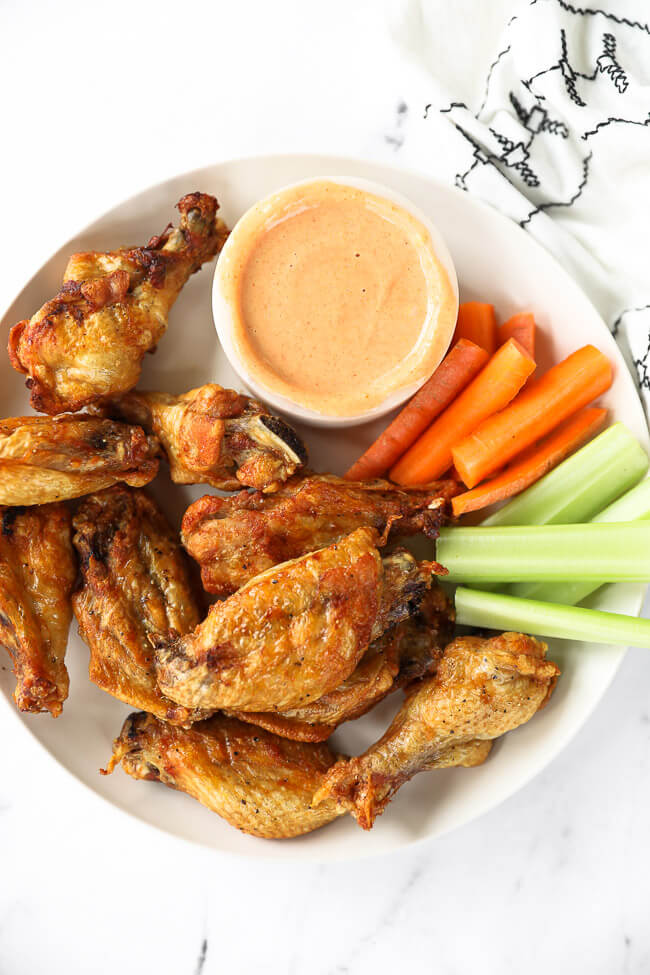 Air fryer chicken wings on a plate with buffalo sauce, carrots and celery