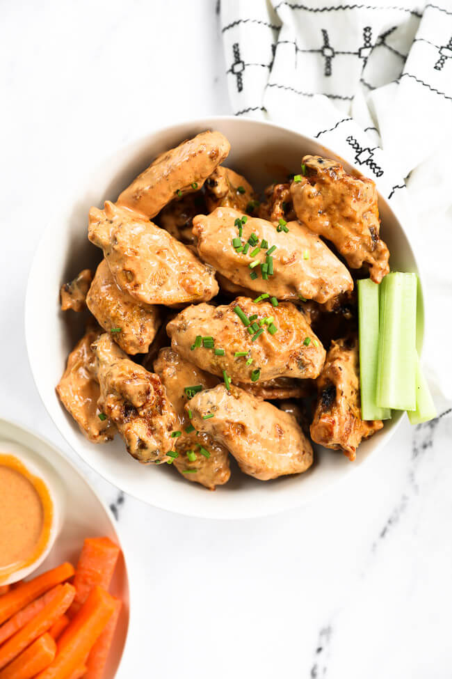 Bowl of chicken wings tossed in creamy buffalo sauce and diced chives topping bowl