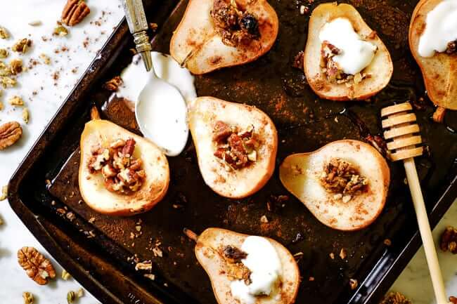 Easy baked pears on a cookie sheet with cinnamon, chopped nuts, granola, honey and coconut yogurt.