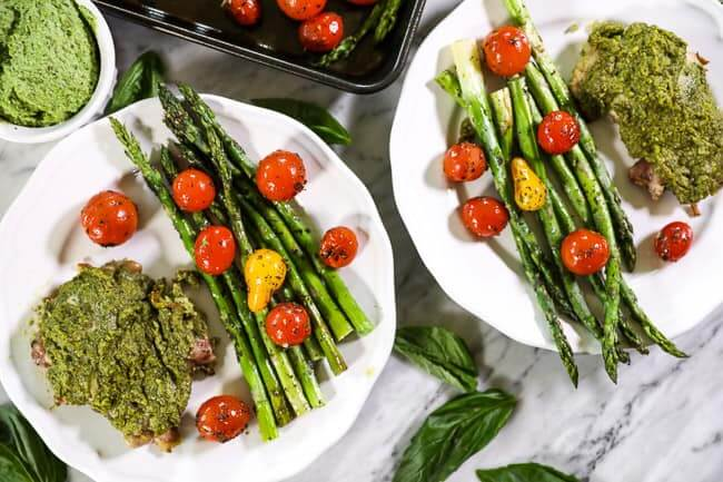 Easy baked pesto chicken on plates with tomatoes and asparagus horizontal image