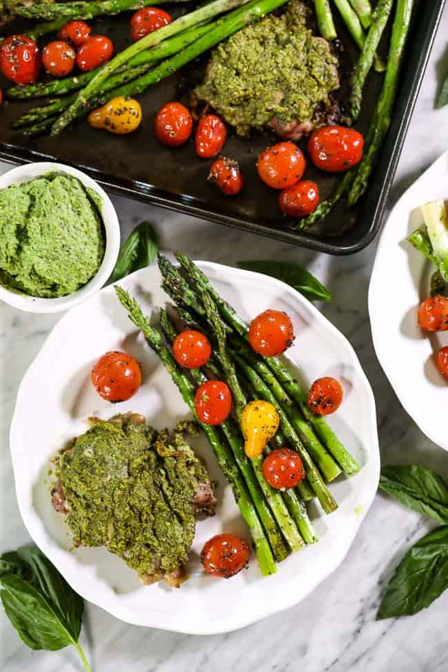 Easy baked pesto chicken on single plate with tomatoes and asparagus sheet pan on top of image