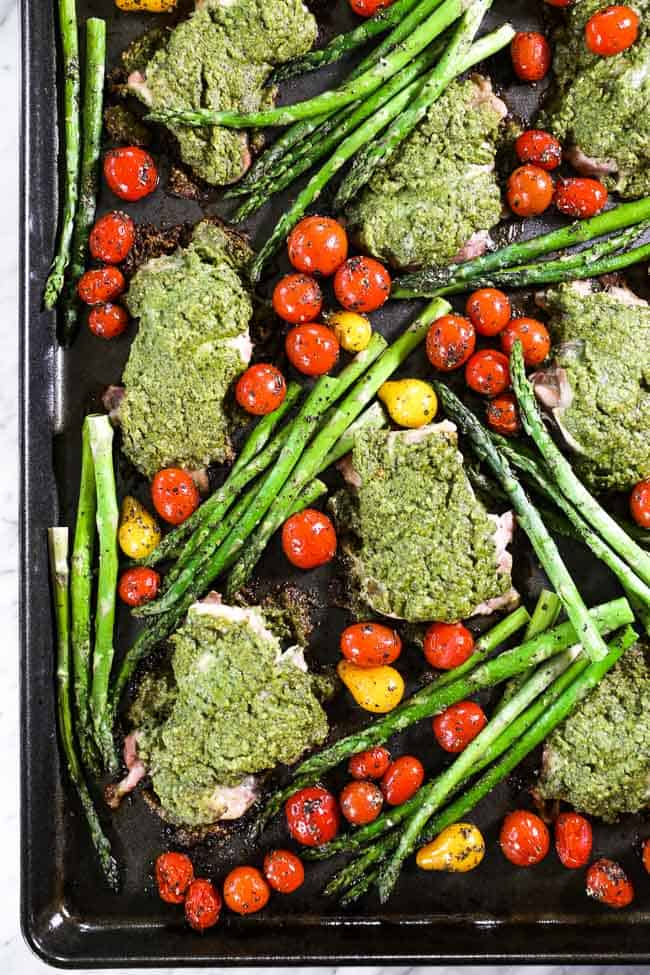 Pesto chicken on a sheet pan with asparagus and tomatoes around it