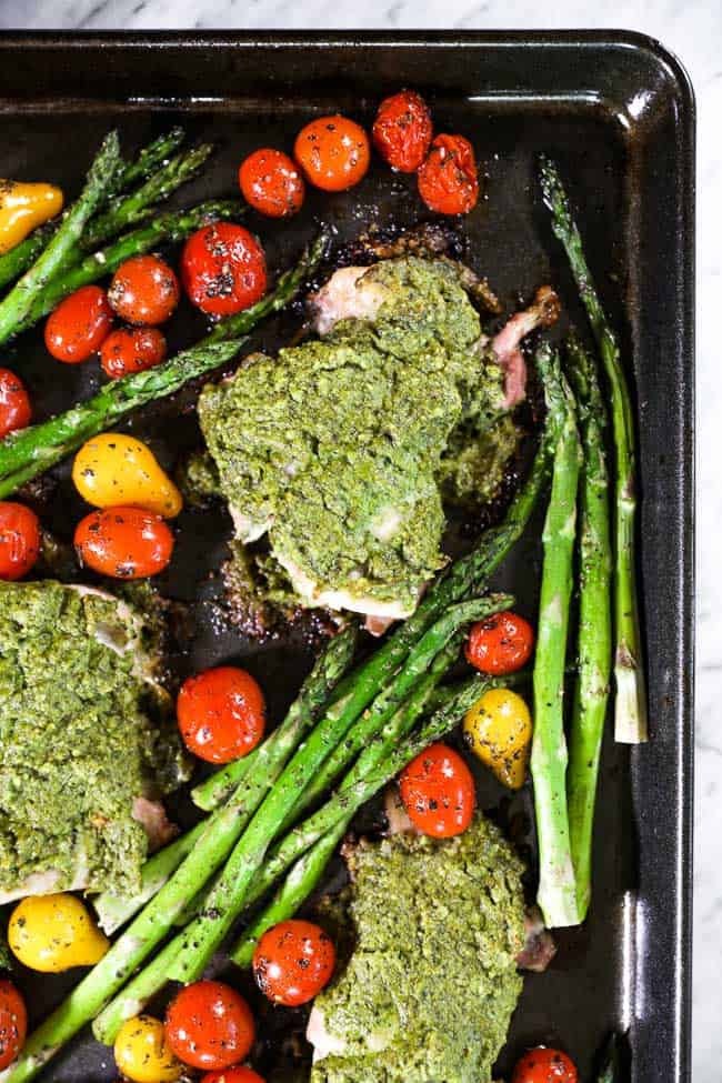 Easy baked pesto chicken on sheet pan with tomatoes and asparagus close up image