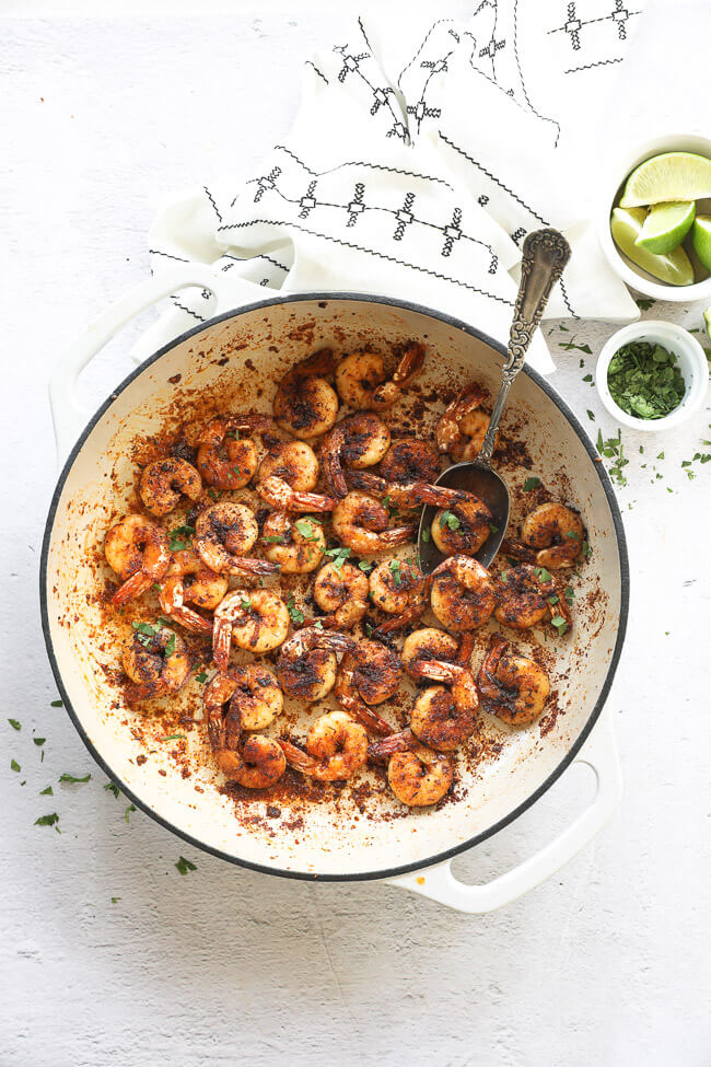 Overhead vertical image of blackened shrimp in a skillet with fresh chopped cilantro sprinkled on top and a spoon like it's scooping shrimp out.