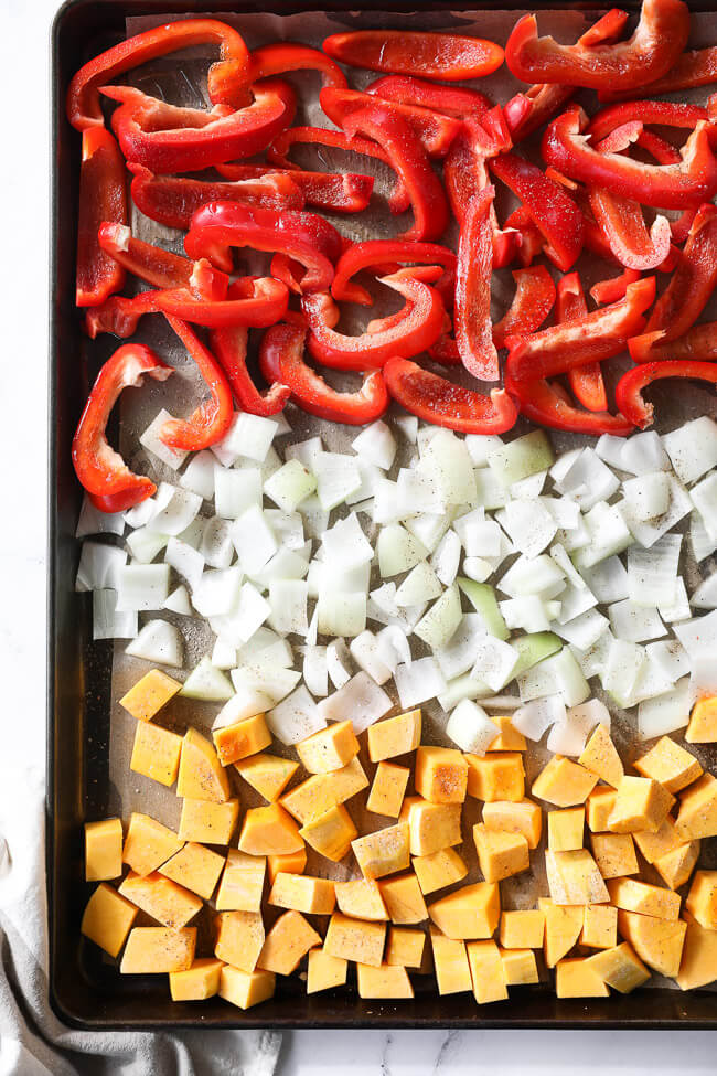 A sheet pan with chopped red bell peppers, onion and butternut squash.