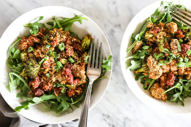 Easy chicken and chorizo bake with greens in bowls and fork overhead horizontal shot