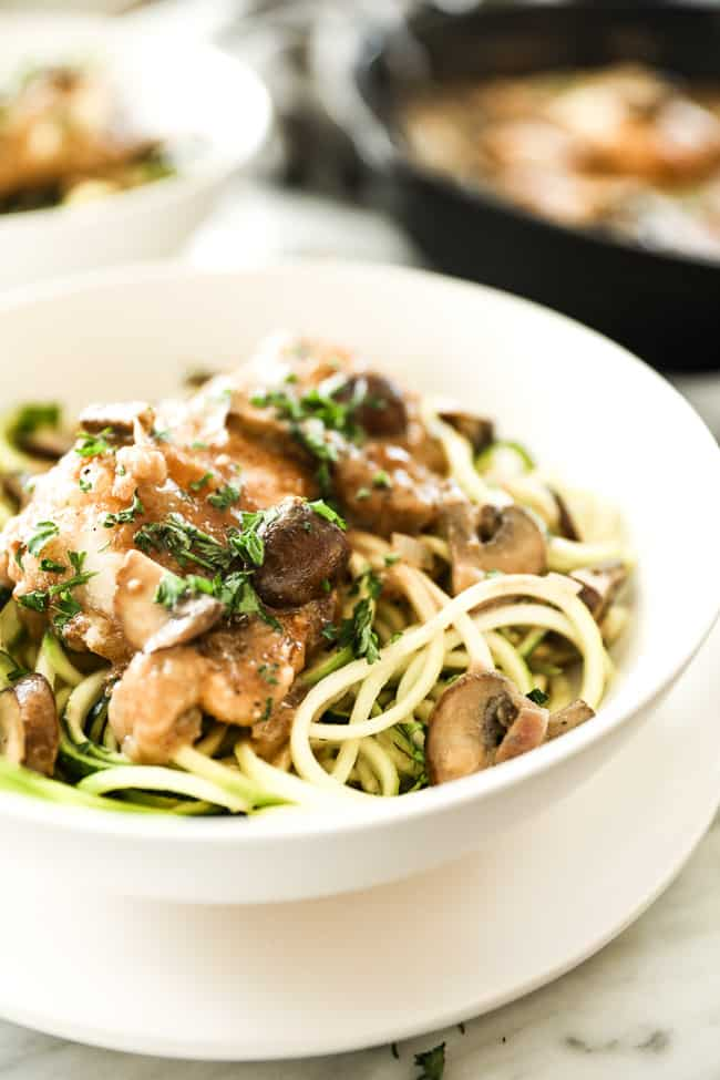 Easy chicken marsala with chicken, mushrooms and a creamy sauce served in a bowl over zucchini noodles. Fresh chopped parsley sprinkled on top.