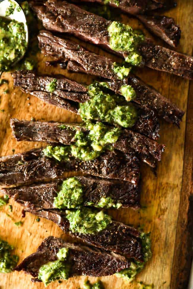 Chimichurri steak sliced and spread out on a cutting board with sauce drizzled on top.